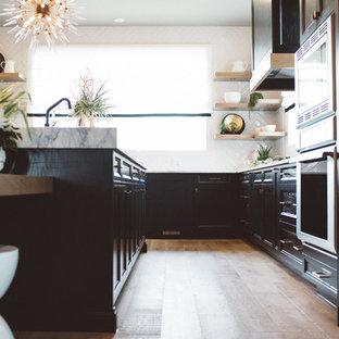 Esempio di una cucina minimalista di medie dimensioni con lavello sottopiano, ante con riquadro incassato, ante nere, top in marmo, paraspruzzi bianco, paraspruzzi con piastrelle in ceramica, elettrodomestici in acciaio inossidabile, moquette, isola, pavimento grigio e top grigio