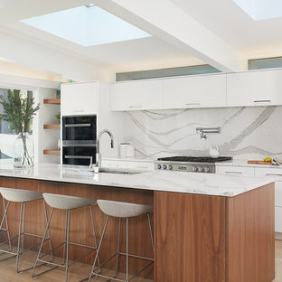 Photo of an expansive midcentury galley kitchen in Grand Rapids with an undermount sink, flat-panel cabinets, white cabinets, white splashback, stone slab splashback, panelled appliances, light hardwood floors, with island, white benchtop and beige floor.
