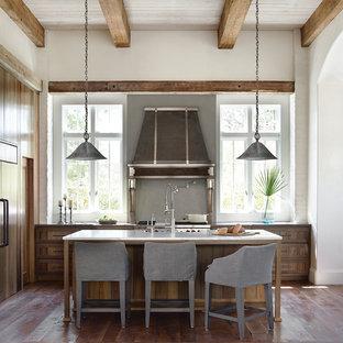 Ejemplo de cocina marinera con puertas de armario de madera oscura, salpicadero verde, electrodomésticos con paneles, suelo de madera en tonos medios y una isla