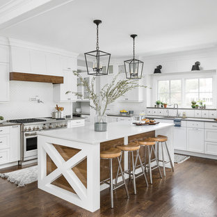 Farmhouse eat-in kitchen appliance - Eat-in kitchen - country u-shaped medium tone wood floor and brown floor eat-in kitchen idea in Chicago with an undermount sink, shaker cabinets, white cabinets, white backsplash, stainless steel appliances, an island and white countertops