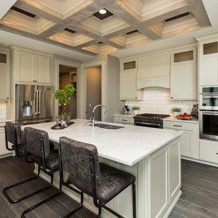 他の地域の中くらいのトランジショナルスタイルのおしゃれなキッチン (ダブルシンク、シェーカースタイル扉のキャビネット、白いキャビネット、大理石カウンター、白いキッチンパネル、シルバーの調理設備、磁器タイルの床、茶色い床、白いキッチンカウンター) の写真