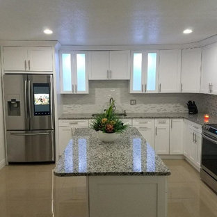 Photo of a large modern galley kitchen/diner in Tampa with a double-bowl sink, flat-panel cabinets, white cabinets, granite worktops, multi-coloured splashback, cement tile splashback, stainless steel appliances, cement flooring, an island, brown floors and grey worktops.