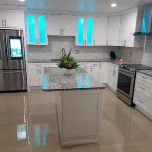 This is an example of a large modern galley kitchen/diner in Tampa with a double-bowl sink, flat-panel cabinets, white cabinets, granite worktops, multi-coloured splashback, cement tile splashback, stainless steel appliances, cement flooring, an island, brown floors and grey worktops.