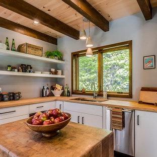 ボストンの小さいモダンスタイルのおしゃれなキッチン (アンダーカウンターシンク、フラットパネル扉のキャビネット、白いキャビネット、木材カウンター、シルバーの調理設備の、セラミックタイルの床、茶色い床、茶色いキッチンカウンター) の写真