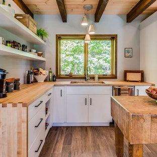 ボストンの小さいモダンスタイルのおしゃれなキッチン (アンダーカウンターシンク、フラットパネル扉のキャビネット、白いキャビネット、木材カウンター、シルバーの調理設備、セラミックタイルの床、茶色い床、茶色いキッチンカウンター) の写真