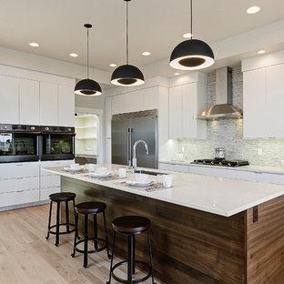 Foto di una cucina a L minimalista con lavello sottopiano, ante lisce, ante bianche, paraspruzzi grigio, elettrodomestici in acciaio inossidabile, parquet chiaro, isola, pavimento beige e top bianco