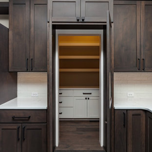 This is an example of a transitional u-shaped eat-in kitchen in Other with an undermount sink, shaker cabinets, medium wood cabinets, quartz benchtops, white splashback, ceramic splashback, stainless steel appliances, carpet, multiple islands, brown floor and white benchtop.