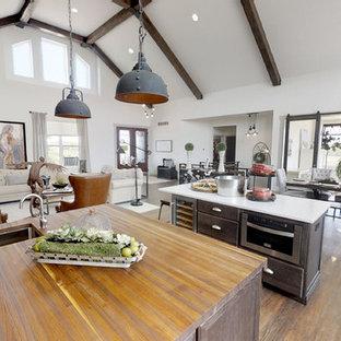 他の地域の大きいインダストリアルスタイルのおしゃれなキッチン (無垢フローリング、白い床、エプロンフロントシンク、シルバーの調理設備の、シェーカースタイル扉のキャビネット、茶色いキャビネット、人工大理石カウンター、マルチカラーのキッチンパネル、レンガのキッチンパネル、マルチカラーのキッチンカウンター) の写真