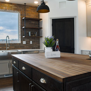 Inspiration for a large industrial u-shaped open plan kitchen in Other with a farmhouse sink, shaker cabinets, white cabinets, quartz benchtops, white splashback, brick splashback, stainless steel appliances, vinyl floors, multiple islands, brown floor and white benchtop.