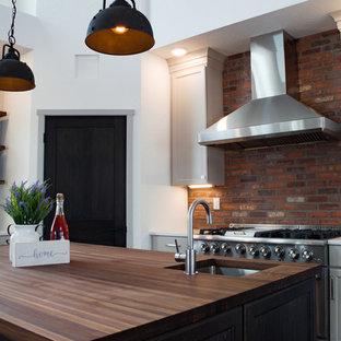 他の地域の大きいインダストリアルスタイルのおしゃれなキッチン (エプロンフロントシンク、シェーカースタイル扉のキャビネット、白いキャビネット、クオーツストーンカウンター、白いキッチンパネル、レンガのキッチンパネル、シルバーの調理設備、クッションフロア、茶色い床、白いキッチンカウンター) の写真