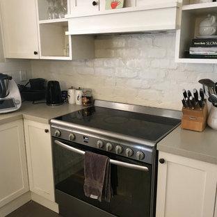 他の地域の中くらいのモダンスタイルのおしゃれなキッチン (シェーカースタイル扉のキャビネット、白いキャビネット、クオーツストーンカウンター、白いキッチンパネル、レンガのキッチンパネル、シルバーの調理設備、セラミックタイルの床、茶色い床、ベージュのキッチンカウンター) の写真