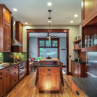 Large craftsman enclosed kitchen appliance - Example of a large arts and crafts galley medium tone wood floor and brown floor enclosed kitchen design in Portland with a farmhouse sink, shaker cabinets, soapstone countertops, green backsplash, ceramic backsplash, stainless steel appliances, an island, medium tone wood cabinets and black countertops