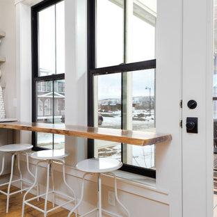 他の地域の広いカントリー風おしゃれなキッチン (エプロンフロントシンク、シェーカースタイル扉のキャビネット、グレーのキャビネット、クオーツストーンカウンター、黄色いキッチンパネル、レンガのキッチンパネル、シルバーの調理設備、クッションフロア、茶色い床、白いキッチンカウンター) の写真
