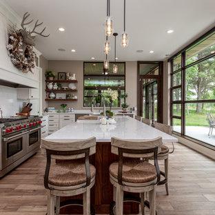 Inredning av ett rustikt mellanstort vit vitt kök, med en köksö, skåp i shakerstil, vita skåp, vitt stänkskydd, stänkskydd i sten, rostfria vitvaror och mellanmörkt trägolv