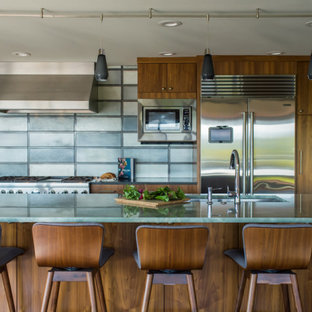 This is an example of a mid-sized midcentury single-wall open plan kitchen in Seattle with an undermount sink, flat-panel cabinets, medium wood cabinets, quartz benchtops, multi-coloured splashback, stainless steel appliances, medium hardwood floors, with island, brown floor and green benchtop.