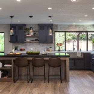 Idéer för att renovera ett mellanstort industriellt linjärt kök med öppen planlösning, med en rustik diskho, luckor med infälld panel, blå skåp, granitbänkskiva, grått stänkskydd, stänkskydd i keramik, rostfria vitvaror, vinylgolv, en köksö och brunt golv