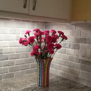 Modelo de cocina en U, costera, pequeña, abierta, con fregadero bajoencimera, puertas de armario blancas, salpicadero blanco, salpicadero de azulejos de piedra, electrodomésticos de acero inoxidable, armarios estilo shaker, encimera de madera y suelo de terrazo
