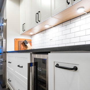 Inspiration for a small modern galley separate kitchen in New York with an undermount sink, shaker cabinets, white cabinets, white splashback, subway tile splashback, stainless steel appliances, vinyl floors and no island.