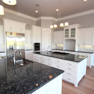 Large transitional eat-in kitchen ideas - Eat-in kitchen - large transitional u-shaped light wood floor eat-in kitchen idea in Dallas with an undermount sink, recessed-panel cabinets, white cabinets, granite countertops, white backsplash, stainless steel appliances and two islands