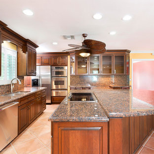 Expansive beach style l-shaped eat-in kitchen in Miami with a drop-in sink, raised-panel cabinets, medium wood cabinets, granite benchtops, multi-coloured splashback, stainless steel appliances, terra-cotta floors, with island, pink floor and multi-coloured benchtop.