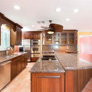 Geräumige Maritime Wohnküche in L-Form mit Einbauwaschbecken, profilierten Schrankfronten, hellbraunen Holzschränken, Granit-Arbeitsplatte, bunter Rückwand, Küchengeräten aus Edelstahl, Terrakottaboden, Kücheninsel, rosa Boden und bunter Arbeitsplatte in Miami