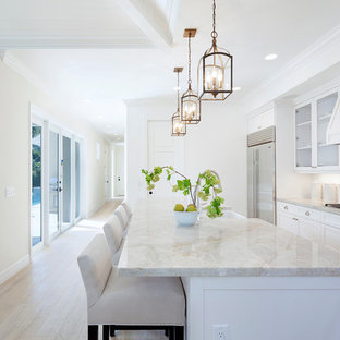 Traditional kitchen photos - Kitchen - traditional light wood floor kitchen idea in Miami with a farmhouse sink, shaker cabinets, white cabinets, white backsplash, subway tile backsplash, stainless steel appliances and an island