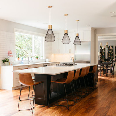 Inspiration for a large transitional u-shaped medium tone wood floor and brown floor open concept kitchen remodel in Seattle with shaker cabinets, white cabinets, quartz countertops, an island, white countertops, an undermount sink, white backsplash, subway tile backsplash and stainless steel appliances