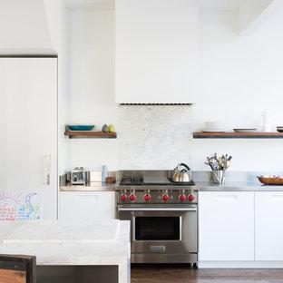 サンフランシスコの広いエクレクティックスタイルのおしゃれなキッチン (ドロップインシンク、フラットパネル扉のキャビネット、白いキャビネット、ステンレスカウンター、白いキッチンパネル、大理石のキッチンパネル、シルバーの調理設備、無垢フローリング、茶色い床) の写真