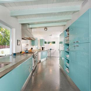マイアミの中くらいのミッドセンチュリースタイルのおしゃれなキッチン (アンダーカウンターシンク、フラットパネル扉のキャビネット、ターコイズのキャビネット、コンクリートカウンター、コンクリートの床、グレーの床、グレーのキッチンカウンター、シルバーの調理設備、アイランドなし) の写真