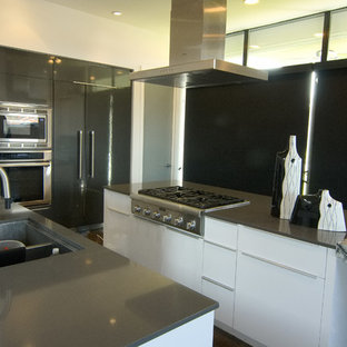 This is an example of a large modern u-shaped kitchen/diner with a double-bowl sink, flat-panel cabinets, white cabinets, granite worktops, grey splashback, mosaic tiled splashback, coloured appliances, concrete flooring, an island, brown floors and grey worktops.