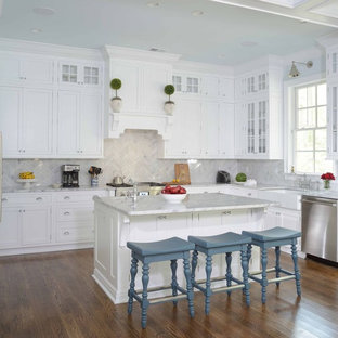 Traditional kitchen inspiration - Kitchen - traditional l-shaped dark wood floor kitchen idea in Charleston with a farmhouse sink, shaker cabinets, white cabinets, white backsplash, stainless steel appliances and an island