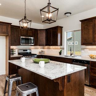 Foto på ett mellanstort vintage beige kök, med en undermonterad diskho, skåp i shakerstil, skåp i mörkt trä, bänkskiva i kvarts, beige stänkskydd, stänkskydd i tunnelbanekakel, rostfria vitvaror, laminatgolv, en köksö och gult golv