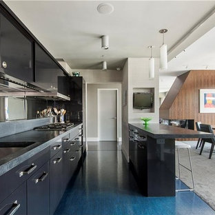 Large contemporary open concept kitchen photos - Example of a large trendy single-wall cork floor open concept kitchen design in New York with flat-panel cabinets, black cabinets, concrete countertops, metallic backsplash, stainless steel appliances and an island