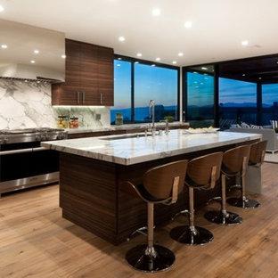 Modelo de cocina en L, moderna, grande, abierta, con fregadero de un seno, armarios con paneles lisos, puertas de armario de madera en tonos medios, encimera de mármol, salpicadero blanco, salpicadero de mármol, electrodomésticos con paneles, suelo de madera clara y una isla