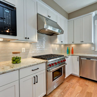 Transitional kitchen inspiration - Kitchen - transitional l-shaped light wood floor kitchen idea in DC Metro with shaker cabinets, white cabinets, gray backsplash, stainless steel appliances and an island