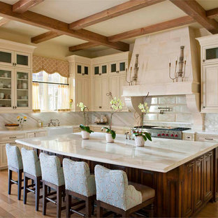 Elegant l-shaped kitchen photo in Dallas with a farmhouse sink, raised-panel cabinets, beige cabinets, beige backsplash and marble backsplash