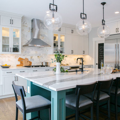 Inspiration for a large transitional brown floor and dark wood floor kitchen remodel in Denver with an undermount sink, shaker cabinets, white cabinets, quartz countertops, marble backsplash, stainless steel appliances, an island, white countertops and white backsplash