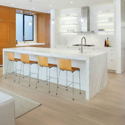 Example of a large trendy l-shaped light wood floor open concept kitchen design in San Francisco with open cabinets, white cabinets, white backsplash, paneled appliances, an island, an undermount sink, marble countertops and stone slab backsplash