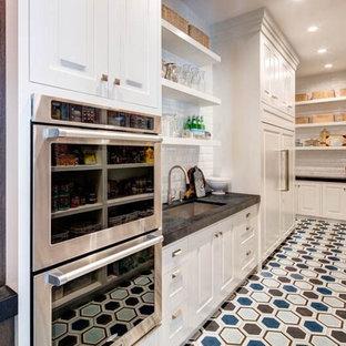 オレンジカウンティの巨大なトランジショナルスタイルのおしゃれなキッチン (ドロップインシンク、グレーのキャビネット、大理石カウンター、白いキッチンパネル、パネルと同色の調理設備、無垢フローリング) の写真