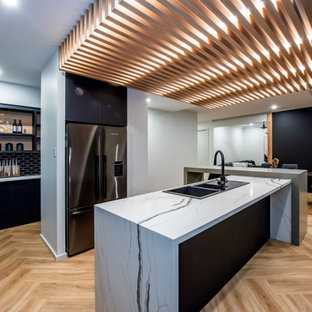 Contemporary l-shaped eat-in kitchen in Other with a double-bowl sink, flat-panel cabinets, black cabinets, black splashback, stainless steel appliances, light hardwood floors, with island, beige floor and multi-coloured benchtop.