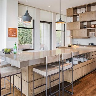 This is an example of a large contemporary u-shaped kitchen in New York with flat-panel cabinets, medium wood cabinets, quartz benchtops, white splashback, glass sheet splashback, stainless steel appliances, with island, brown floor, beige benchtop and dark hardwood floors.