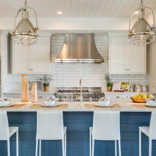 Modelo de cocina costera con armarios estilo shaker, puertas de armario blancas, salpicadero blanco, salpicadero de azulejos tipo metro, electrodomésticos de acero inoxidable y una isla