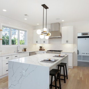 Transitional kitchen photos - Kitchen - transitional u-shaped light wood floor and beige floor kitchen idea in New York with an undermount sink, shaker cabinets, white cabinets, white backsplash, stainless steel appliances, an island and white countertops