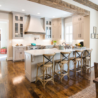 Inspiration for a medium sized traditional u-shaped kitchen/diner in Atlanta with a belfast sink, shaker cabinets, grey cabinets, white splashback, ceramic splashback, stainless steel appliances and medium hardwood flooring.