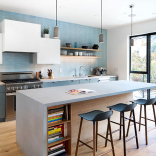 Contemporary kitchen remodeling - Inspiration for a contemporary galley light wood floor kitchen remodel in San Francisco with flat-panel cabinets, blue cabinets, concrete countertops, blue backsplash, stainless steel appliances and an island