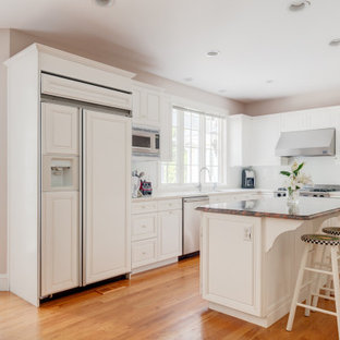 Large traditional kitchen pictures - Kitchen - large traditional l-shaped medium tone wood floor and orange floor kitchen idea in Boston with raised-panel cabinets, white cabinets, solid surface countertops, white backsplash, an island, white countertops, an undermount sink and paneled appliances