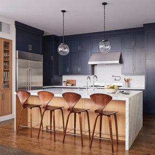 Стильный дизайн: огромная угловая кухня в стиле современная классика с врезной раковиной, фасадами в стиле шейкер, синими фасадами, белым фартуком, техникой из нержавеющей стали, островом, коричневым полом и белой столешницей - последний тренд