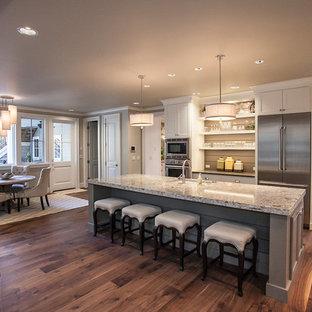 Idéer för ett mellanstort klassiskt kök, med en undermonterad diskho, luckor med infälld panel, vita skåp, granitbänkskiva, flerfärgad stänkskydd, stänkskydd i mosaik, rostfria vitvaror, mörkt trägolv, en köksö och brunt golv