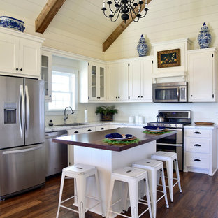 Mid-sized farmhouse kitchen designs - Inspiration for a mid-sized farmhouse l-shaped medium tone wood floor and brown floor kitchen remodel with white cabinets, marble countertops, white backsplash, stainless steel appliances, an island, a single-bowl sink, shaker cabinets and wood backsplash