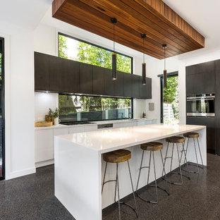 Foto de cocina en L, contemporánea, abierta, con armarios con paneles lisos, puertas de armario negras, salpicadero blanco, salpicadero de vidrio templado, electrodomésticos negros, suelo de terrazo, una isla y suelo gris
